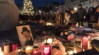 Zum Gedenken an die Opfer werden Kerzen, Blumen und Bilder am Straßburger Weihnachtsmarkt niedergelegt.