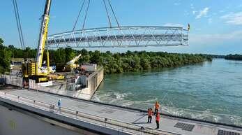 Mit vereinten Kräften platzierten Arbeiter am Mittwochmorgen die Aluminiumbrücke am Kraftwerk auf französischer Seite. Damit ist der aus insgesamt drei Brücken bestehende Fuß- und Radweg zwischen Freistett und Gambsheim fertig.