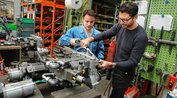 Feinwerkmechaniker Marc Oehler links) zeigt Ortenau-Redakteur Simon Allgeier, wie die Parkbremse an einem hydraulischen Getriebe befestigt wird.