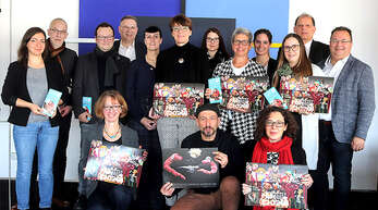 Das Organisationsteam der Puppenparade Ortenau präsentiert den Kalender des Festivals.
