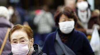 Einige Menschen tragen zum Schutz vor einer Infektion eine Atemmaske.