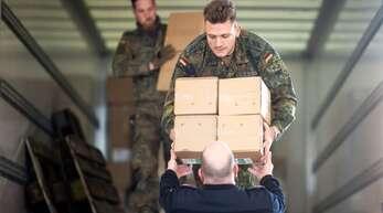 Soldaten und Feuerwehrmänner verladen gemeinsam Kartons mit Schutzkleidung in der Feuerwache Erkelenz.
