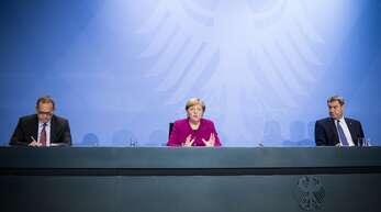 Bundeskanzlerin Angela Merkel (M), Markus Söder (r, CSU), Ministerpräsident von Bayern, und Michael Müller (SPD), Regierender Bürgermeister von Berlin, geben nach einem Treffen mit den Ministerpräsidenten der Länder zu steigenden Infektionszahlen eine Pressekonferenz.