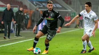 Fokussiert: Freiburgs Torschütze Vincenzo Grifo (l.) behauptet den Ball gegen den Augsburger Rani Khedira.