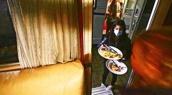 Die Servicekraft Viviane Carlucci holt an der Wohnmobil-Tür den Abwasch ab.