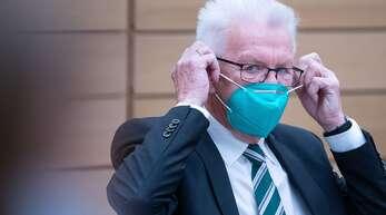 Winfried Kretschmann (Bündnis 90/Die Grünen), Ministerpräsident von Baden-Württemberg, zieht während der Sondersitzung des Landtags von Baden-Württemberg zu den Corona-Beschlüssen von Bund und Ländern seinen Mund- und Nasenschutz aus.