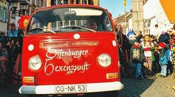 """Wenn die Offenburger Hexenzunft an einem Umzug teilnimmt, ist der rote Bulli mit von der Partie, und das schon seit 50 Jahren. Das Foto zeigt das Fahrzeug mit der """"Rattefall"""" in der Hauptstraße – links das Rathaus, rechts die Ursulasäule."""