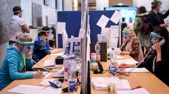 Die deutsche Verwaltung hat Weltruf, nur in der Krise hapert's in vielen Amtsstuben. Das Bild zeigt Mitarbeiter des Gesundheitsamts Berlin-Mitte mit Gesichtsschutzschirmen.
