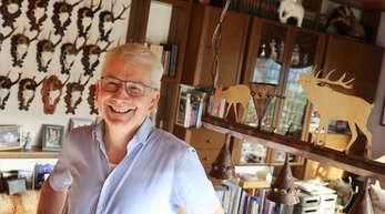 Rainer Moritz, der frühere Leiter des Landwirtschaftsamts, steht in seinem Wohnzimmer. Auch mit der Raum-Deko macht er deutlich, dass die Jagd zu seinen Hobbys zählt.