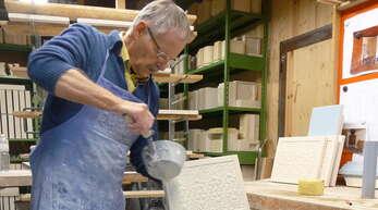 Johann Schreiber bei der Bearbeitung handgeformter Ofenkacheln mit keramischem Ton.
