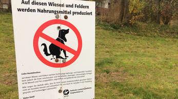 Landwirte stellen Schilder auf, um Hundehalter für das Thema Hundekot zu sensibilisieren.
