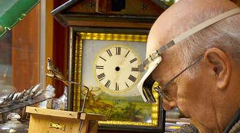 Uhrmachermeister Hermann Uhl (81) aus Gengenbach untersucht das Werk einer mit Hirschen bemalten Schwarzwalduhr.