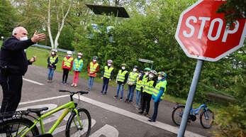 Polizist Hans Peter Huber erklärt den Mädchen und Jungen der 4a der Schutterwälder Mörburgschule ein Stop-Schild.