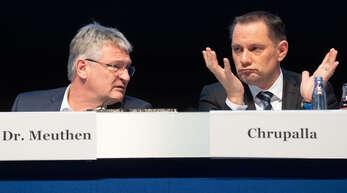 Jörg Meuthen (li) und Tino Chrupalla, beide Bundessprecher der AfD, sitzen bei einem Parteitag der AfD auf dem Podium.