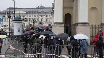 Menschen warten in einer Schlange vor dem Warschauer Rathaus auf ihre Impfung. Foto: Aleksander Kalka/ZUMA Wire/dpa