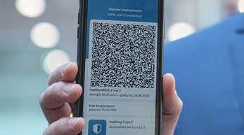Gesundheitsminister Jens Spahn (CDU) zeigt die App zum digitalen Impfpass bei der Pressekonferenz zur Corona-Lage am Donnerstag. Ab Montag werden die Apotheken dafür zuständig sein, dieses Zertifikat bereitzustellen.