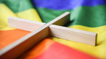 Ein Holzkreuz auf der Regenbogenfahne, dem Symbol für die Vielfalt von Schwulen und Lesben in aller Welt – die konservative Haltung der Katholischen Kirche in Rom stößt bei vielen Christen in der Region für Unverständnis.