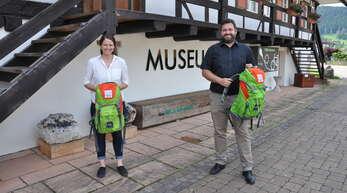 """Touristik-Leiterin Carina Gallus und Bürgermeister Matthias Bauernfeind präsentieren vor dem Museum für Mineralien und Mathematik """"Annis Schwarzwald Geheimnis"""". Die Rücksäcke sind mit Rätsel gefüllt, die ans Ziel führen."""