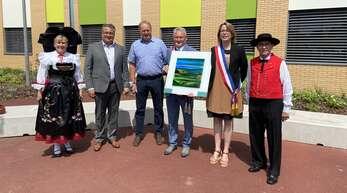 Gerhard Moser und Jochen Strosack überreichen dem ersten Beigeordneten Charles Bapst und Bürgermeisterin Michèle Leckler das Gastgeschenk der Gemeinde Neuried (von links nach rechts). Für den schmucken Rahmen sorgt ein Elsässer Trachtenpaar.
