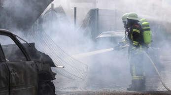 """Mit massivem Wassereinsatz mussten die Wehrleute am Montag beim Brand """"Am alten Ausbesserungswerk"""" vorgehen, um ein Übergreifen des Feuers zu verhindern. Sieben am Straßenrand abgestellte Autos brannten restlos aus."""