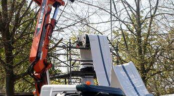 Mit einer Schleife hebt der Kran behutsam den Schlauch aus der Eiskiste auf das Förderrad über dem Turm.