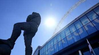 Die Statue von Englands Fußballlegende Bobby Moore steht vor dem UEFA-Euro-Schild am Eingang des Wembley-Stadions. Foto: Frank Augstein/AP/dpa