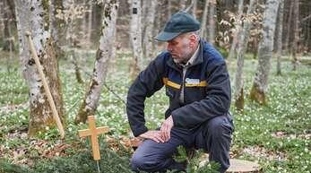 Martin Schuh an einem Grab. Üppige Blumengestecke, Kränze, Laternen, Engelsfiguren – all das sucht man im Friedwald vergeblich. Der Ort soll seinen natürlichen Zustand behalten.