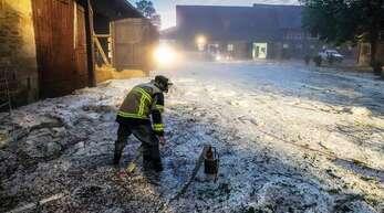 Ein Feuerwehrmann steht in einem Reiterhof in Hagelkörnern.
