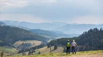 Zwei Frauen stehen nahe dem Nonnenmattweiher auf einem Parkplatz und blicken in die Schwarzwald-Landschaft. Kostet dieses Vergnügen künftig Geld?