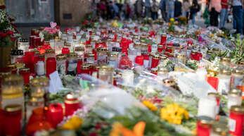 Grablichter, Kerzen und Blumen liegen vor einem Kaufhaus in der Innenstadt von Würzburg.