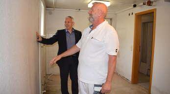 Pfarrer Joachim Giesler bespricht mit einem Maler die Arbeiten im künftigen Obdachlosenzimmer. Es soll mit Spenden renoviert und ausgestattet werden.