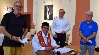Dekan Matthias Bürkle unterschreibt die Pilgerausweise. Links: Norbert Scheiwe, rechts Marcel Oertwig und Gerhard Junker, Vorsitzender der Kinzigtäler Jakobusfreunde.