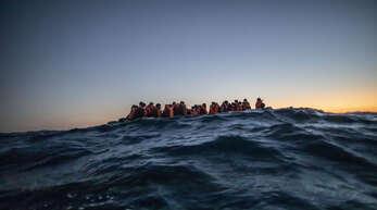Migranten aus verschiedenen afrikanischen Nationen warten in einem Boot auf Helfer der spanischen NGO Open Arms, die sich im ihnen im Februar 122 Meilen vor der libyschen Küste im Mittelmeer nähern.