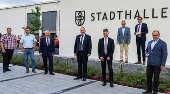Bürgermeister Bernd Siefermann und sein Stellvertreter Heinz Schäfer (Zweiter und Dritter von rechts) enthüllten am Mittwoch im Beisein geladener Gäste den Stadthalle-Schriftzug an der frisch sanierten udn erweiterten Sport- und Festhalle.