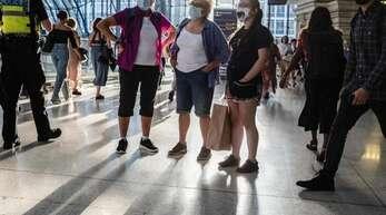 Menschen mit Mund-Nasen-Schutz stehen in einer U-Bahn Station in London. Foto: May James/SOPA Images via ZUMA Press Wire/dpa