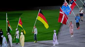 Der Kanute Ronald Rauhe trägt die deutsche Fahne bei der Abschlussfeier in Tokio.
