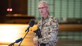 Jens Arlt, Brigadegeneral der Bundeswehr, gibt mit einem Sturmgewehr in der Hand auf dem niedersächsischen Stützpunkt Wunstorf ein Statement ab. Die ersten Soldaten der Bundeswehr sind von ihrer Evakuierungsmission in Afghanistan nach Deutschland zurückgekehrt. Auf dem Luftwaffenstützpunkt Wunstorf bei Hannover landeten am Freitagabend drei Militärmaschinen.