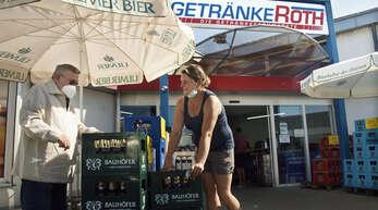 Filialleiterin Amely Homberger berät einen Mann vor dem Getränkemarkt Roth in Kehl. Während des Lockdowns fiel die Hälfte der Kundschaft weg.