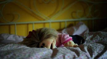 Eine Puppe liegt in einem Kinderzimmer auf dem Bett.