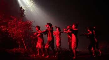 """Lichtblitze durchschneiden die Dunkelheit: Szene aus dem Werk """"Asterism""""."""