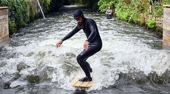"""Surfer Jonas Buchholz steht auf einem Surfbrett in der Anlage """"Blackforestwave"""", die am Freitag offiziell eingeweiht wurde."""
