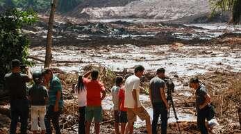 Menschen beobachten die Schlammmassen nach dem Bruch eines Staudamms an der Feijão Eisenerzmine in Brasilien.