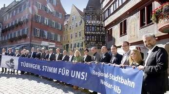 """Die Region steht hinter dem Tübinger Schienenprojekt, signalisieren knapp zwei Dutzend Rathauschefinnen und -chefs. OB Palmer (rechts) appelliert auf dem Marktplatz an die Bürger. """"Selbst wenn Sie die Bahn nicht nutzen, denken Sie solidarisch an die Pendler."""""""