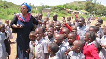 """Projektverantwortliche """"Mama Rosemary"""" mit den Waisenkindern."""