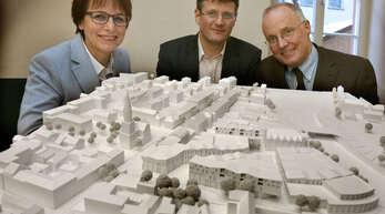 So soll das neue Stadtquartier aussehen: OB Edith Schreiner (von links) und ihre beiden Dezernenten Oliver Martini und Christoph Jopen präsentierten gestern glücklich über die Zuschlagsentscheidung das Modell des neuen Einkaufszentrums.