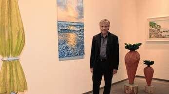 Die Meeresbrandung zeigt das Ölgemälde, vor dem der Künstler Günther Hermann in der Ausstellung in Zell a. H. steht. Rechts und links im Bild sind Skulpturen des Holzbildhauers Ralf Klement zu sehen.
