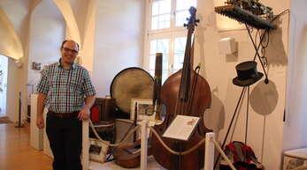 Christian Oberfell, Vorsitzender des Vereins Kultur im Schloss, neben einigen besonderen Stücken der Schau: den alten Musikinstrumenten.