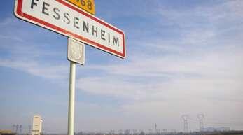 Das Ortsschild von Fessenheim, im Hintergrund das Kernkraftwerk.