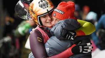 Natalie Geisenberger (l.) und der deutsche Rodel-Bundestrainer Norbert Loch liegen sich vor Freude in den Armen.