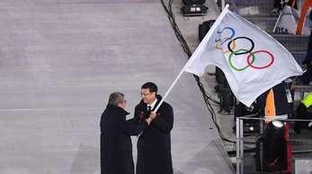 IOC-Präsident Thomas Bach (l) übergibt die olympische Flagge an Pekings Bürgermeister Chen Jining.